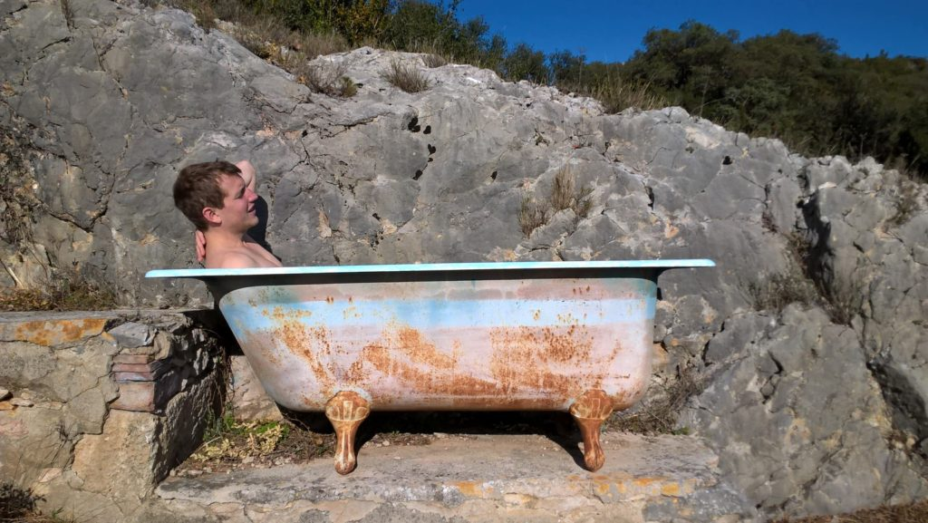 ArchiPol bare chested in an outdoors bathtub